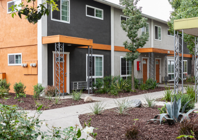 exterior of two story apartment homes at Villa Del Sol with orange details