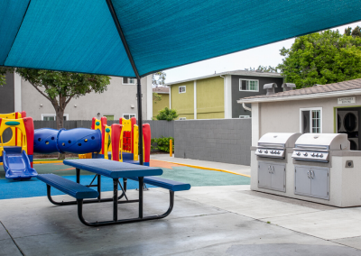 Outdoor BBQ kitchen & picnic areas next to playground and umbrella