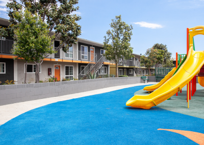 Playground for kids with slide and apartment buildings in background