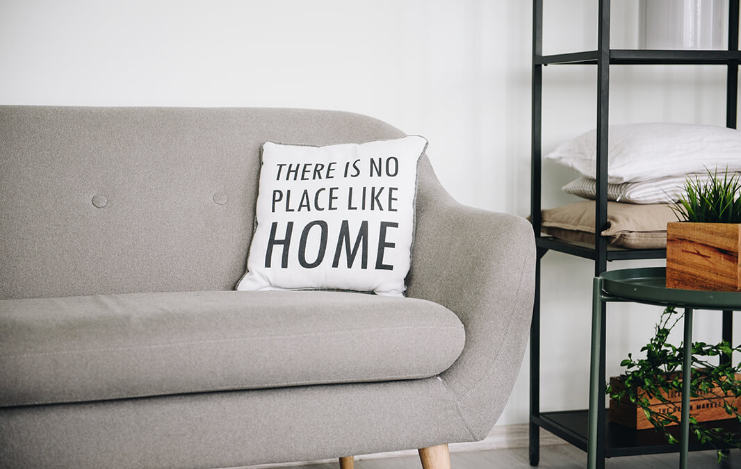 A pillow on a couch that says there is no place like home